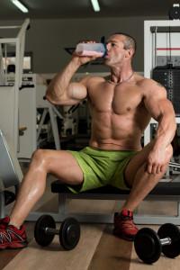 {Bodybuilder drinking protein drink}
